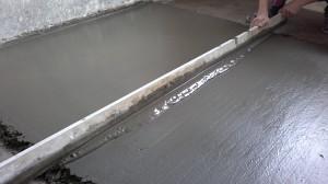 Выравнивание бетонного пола под плитку при помощи правила